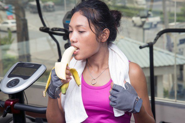Woman Eating Banana at The Gym