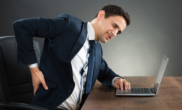 Man in Suit With Back Pain From Sitting