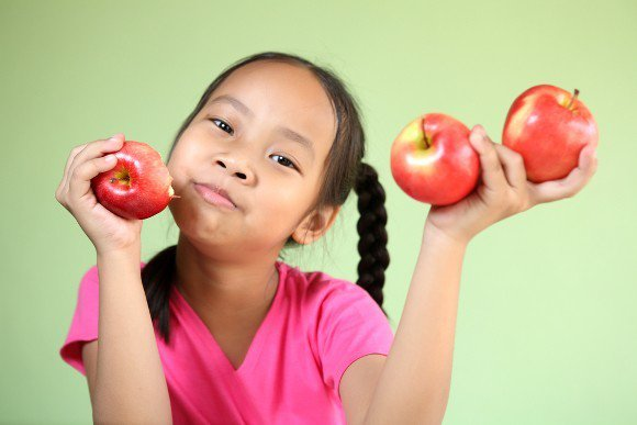 Young Girl Holding Three Apples